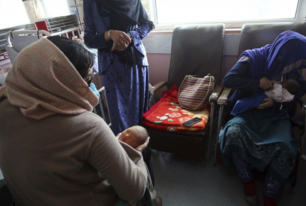 A mother, right, breastfeeds her two-day-old baby at the Ataturk Children's Hospital, a day after they were rescued from a deadly attack on another ma...