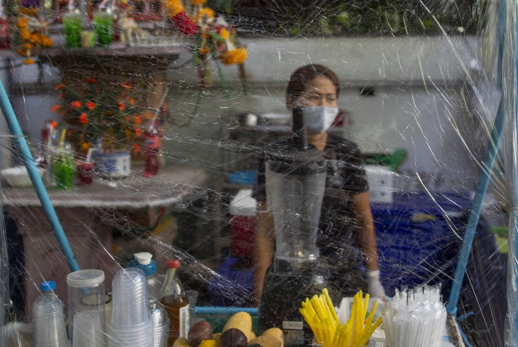 A street food seller stands behind a plastic devider sheet in Bangkok, Thailand, Wednesday, May 13, 2020. Thai government continue to ease restriction...