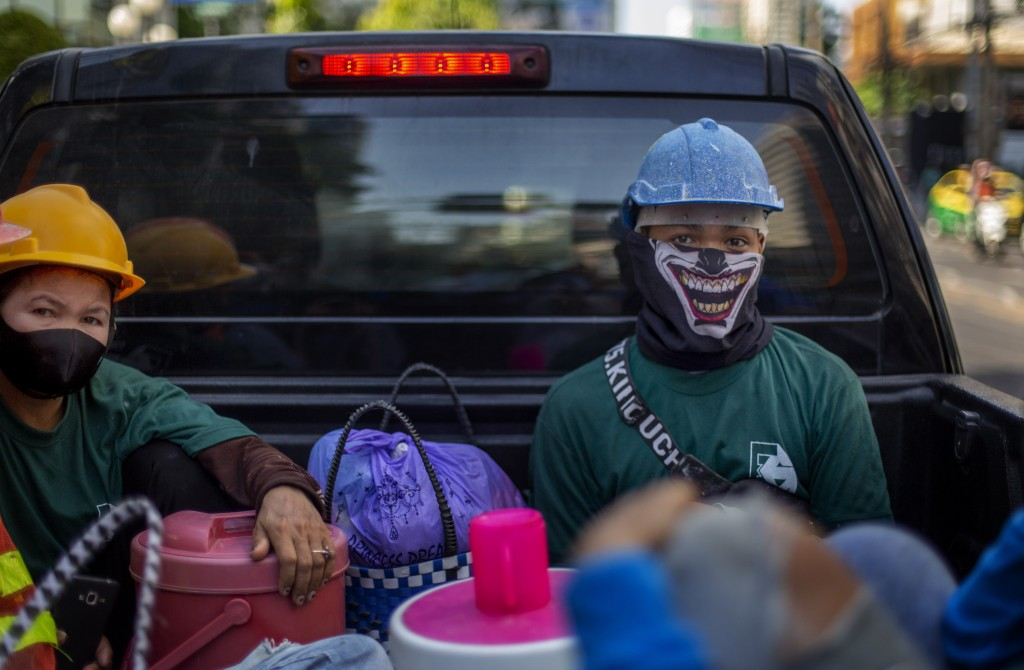 Construction workers wearing face masks travel in a back of a crew cab in Bangkok, Thailand, Wednesday, May 13, 2020. Thai government continue to ease...