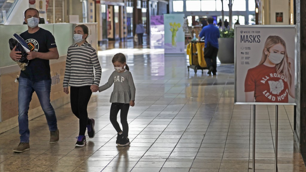 Shoppers walks past a sign encouraging masks at SouthPark Mall, Wednesday, May 13, 2020, in Strongsville, Ohio. Ohio retail businesses reopened Tuesda...