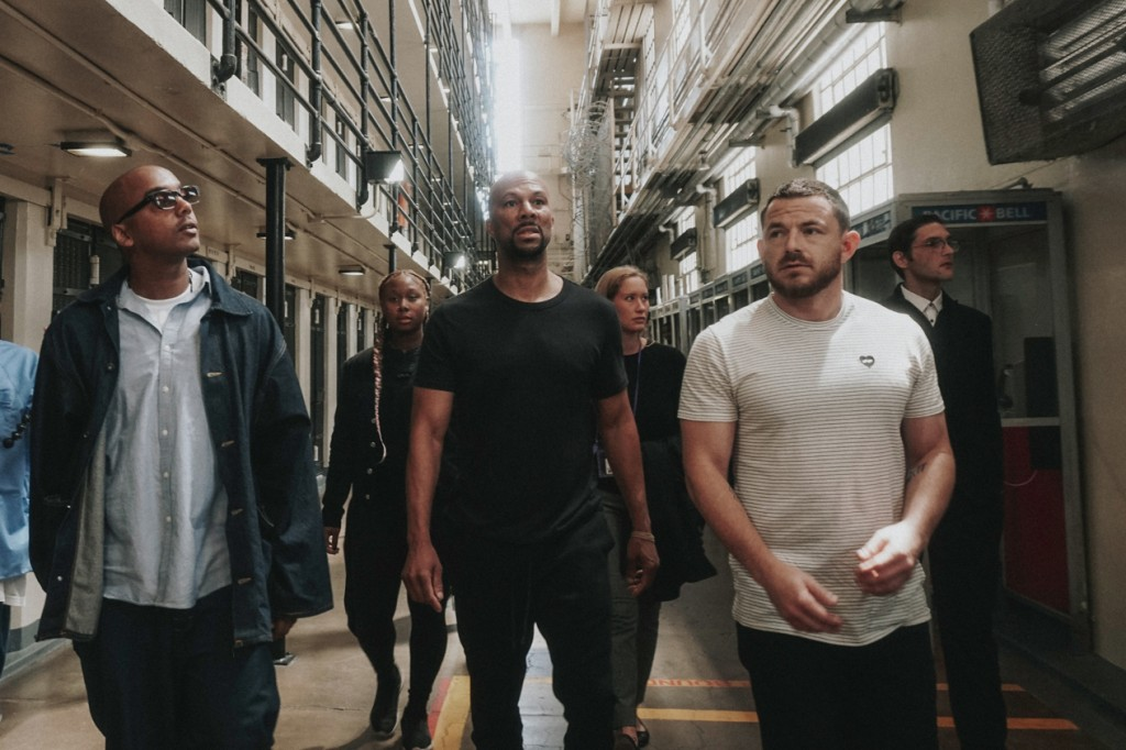 In this Aug. 2, 2018, photo, David Jassy, from left, front, a formerly incarcerated advocate, hip hop artist Common and Imagine Justice political advi...