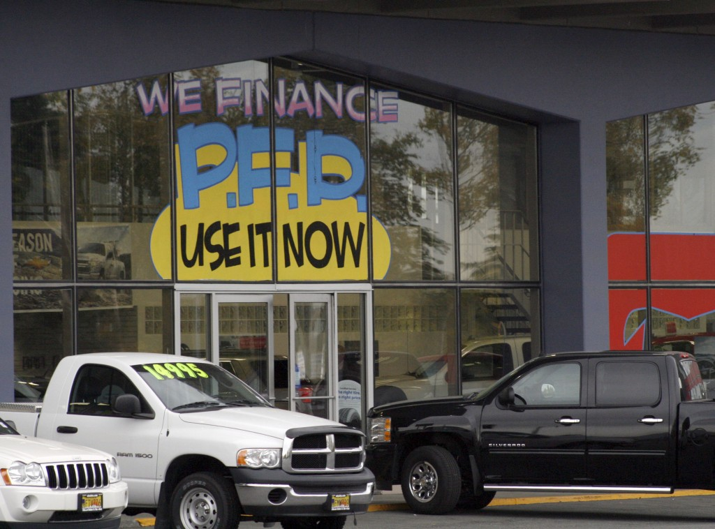 FILE - In this Monday, Sept. 19, 2011 file photo, an auto dealership in Anchorage, Alaska, advertises PFD, or Permanent Fund Dividend, sales. Alaska's...