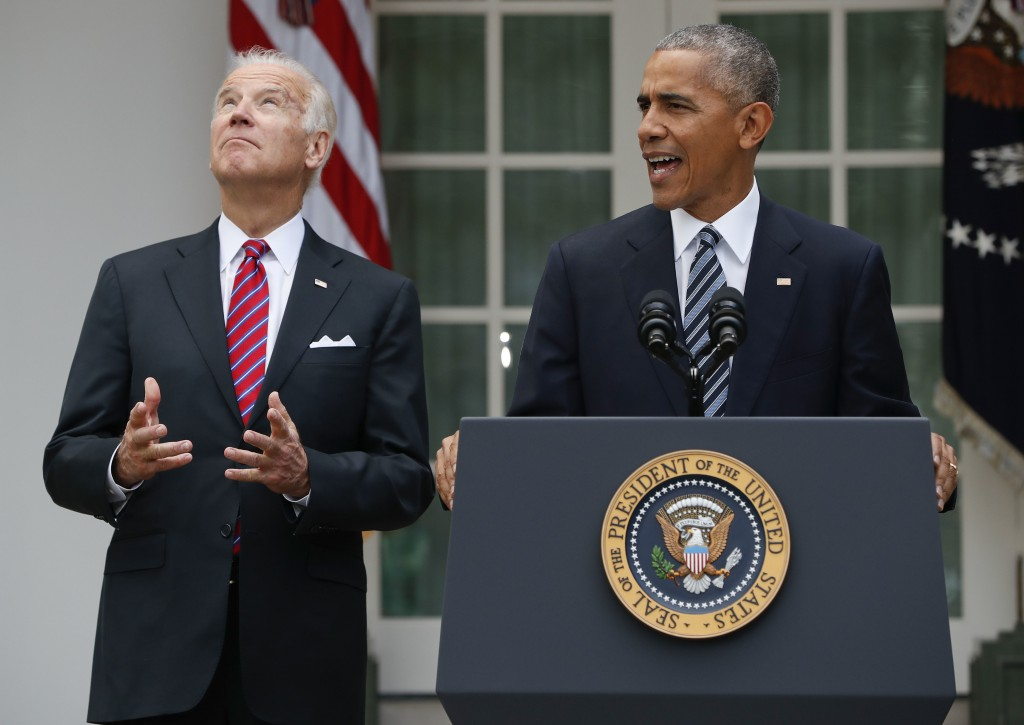 FILE - In this Nov. 9, 2016, file photo, Vice President Joe Biden, left, looks upwards while listening to President Barack Obama speak in the Rose Gar...