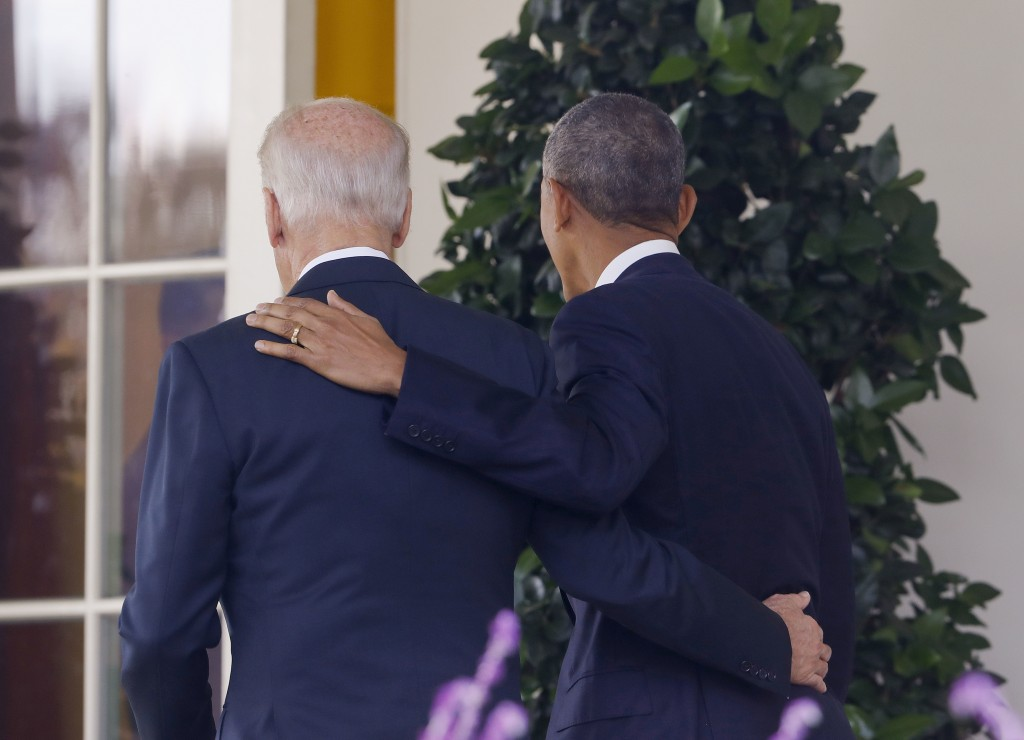 FILE - In this Nov. 9, 2016, file photo, President Barack Obama and Vice President Joe Biden, with their arms on each other, walk back to the Oval Off...