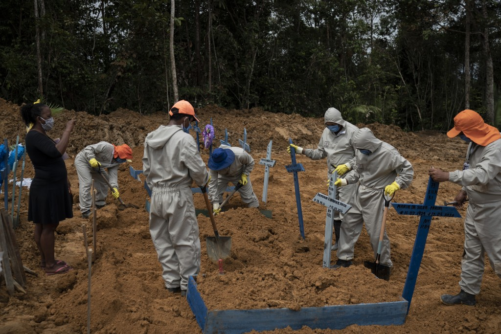 Cemetery workers place crosses over a common grave after burying five people at the Nossa Senhora Aparecida cemetery amid the new coronavirus pandemic...