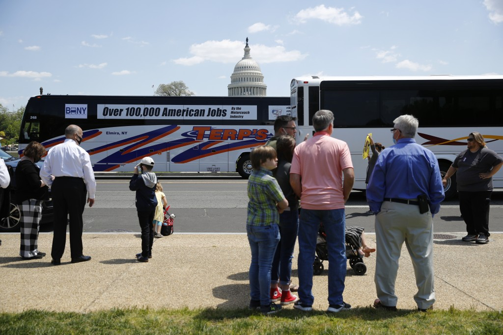 Buses and motor coaches circle past gatherers on the National Mall in Washington, Wednesday, May 13, 2020, as part of a rally to raise awareness of th...