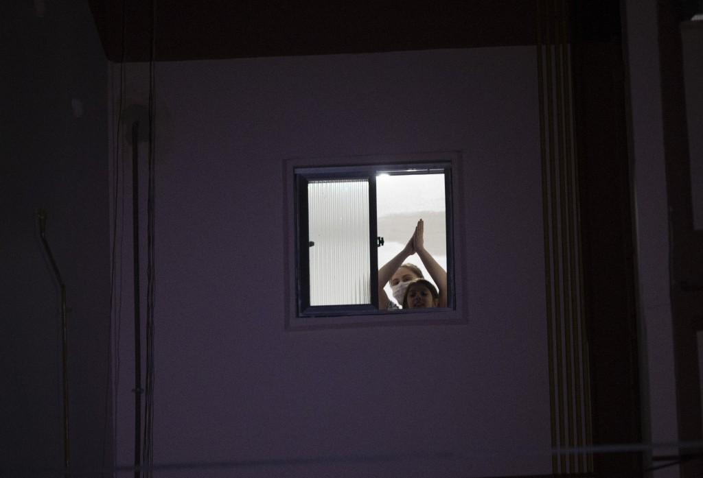 A woman applauds from the window of her apartment as she watches a short film projected on a giant screen placed outdoors in Rio de Janeiro, Brazil, W...