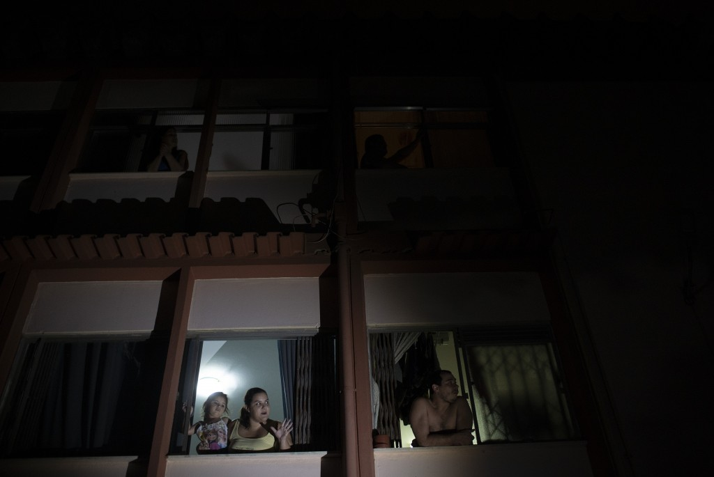 People watch a short film on a giant screen, from their home windows during the new coronavirus pandemic, in Rio de Janeiro, Brazil, Wednesday, May 13...