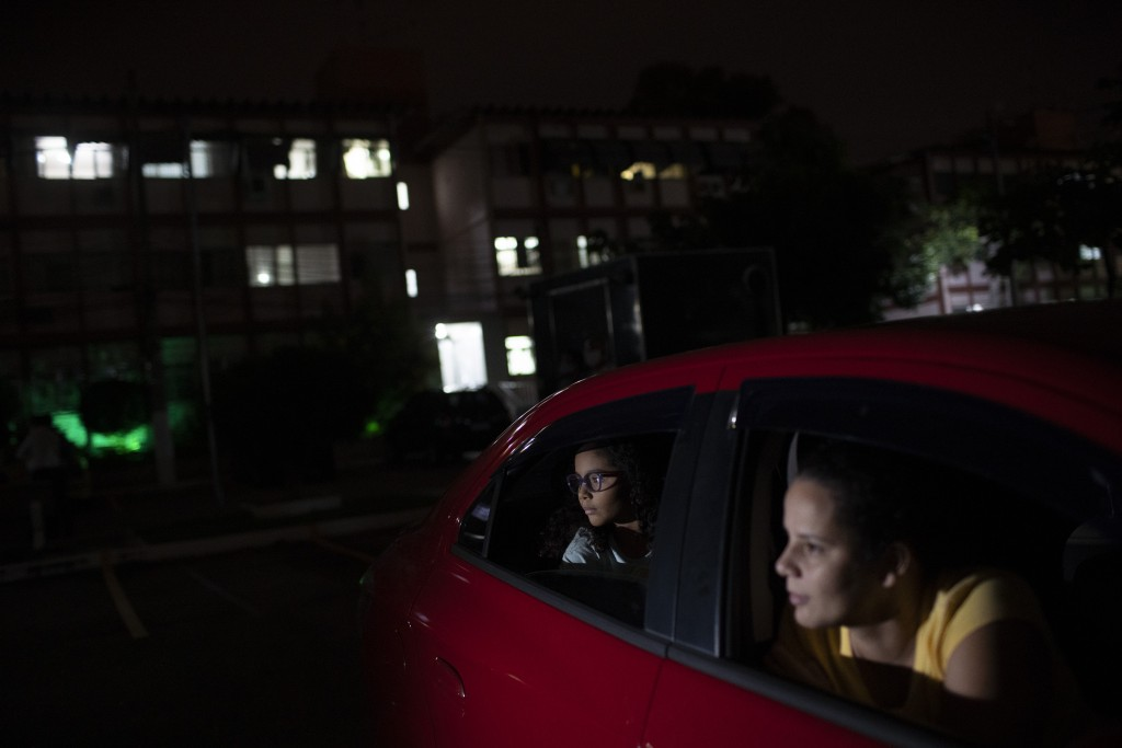Renata, right, and her daughter watch a short film on a giant screen, from their car in Rio de Janeiro, Brazil, Wednesday, May 13, 2020. Cinema from t...
