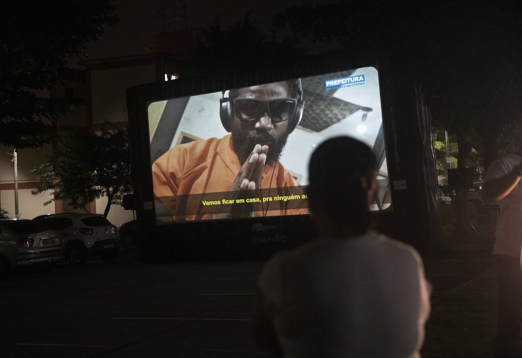 A woman watches a short film on a giant screen in Rio de Janeiro, Brazil, Wednesday, May 13, 2020. Cinema from the windows is the name of a Rio City H...