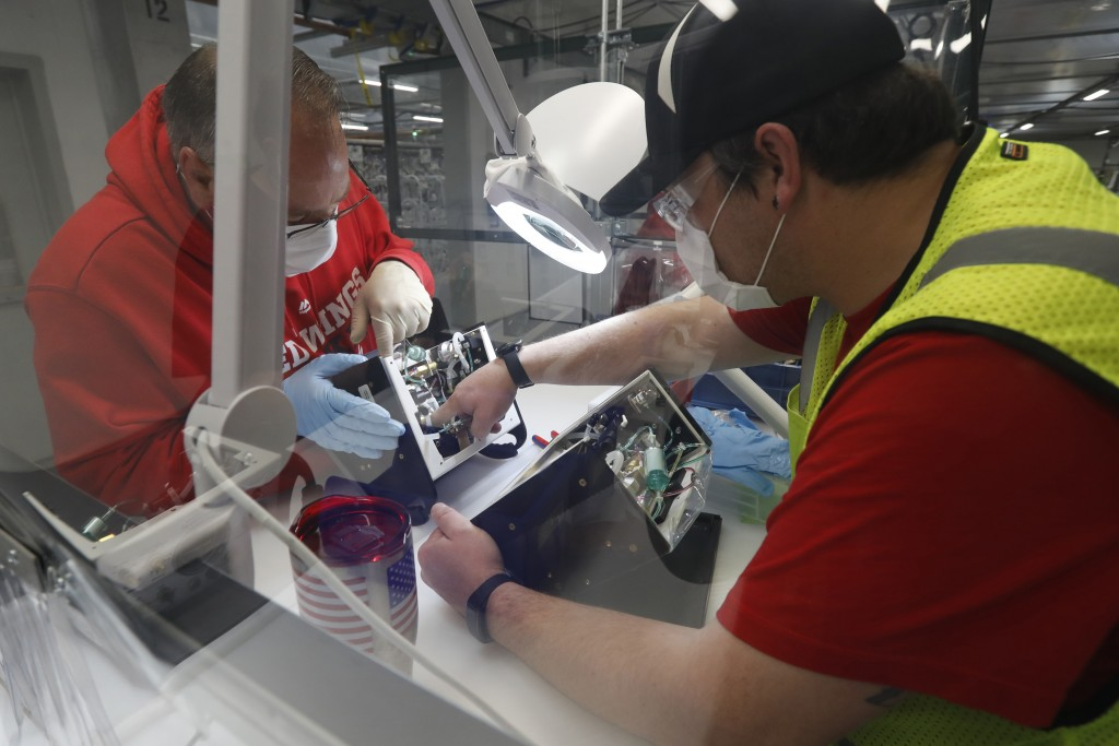 Ford Motor Co., team leader Kyle Lenart, right, inspects a ventilator that the automaker is assembling at the Ford Rawsonville plant, Wednesday, May 1...