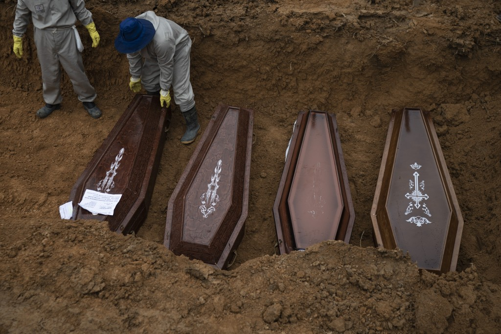 Cemetery workers place coffins in a common grave during a funeral at the Nossa Senhora Aparecida cemetery, amid the new coronavirus pandemic in Manaus...