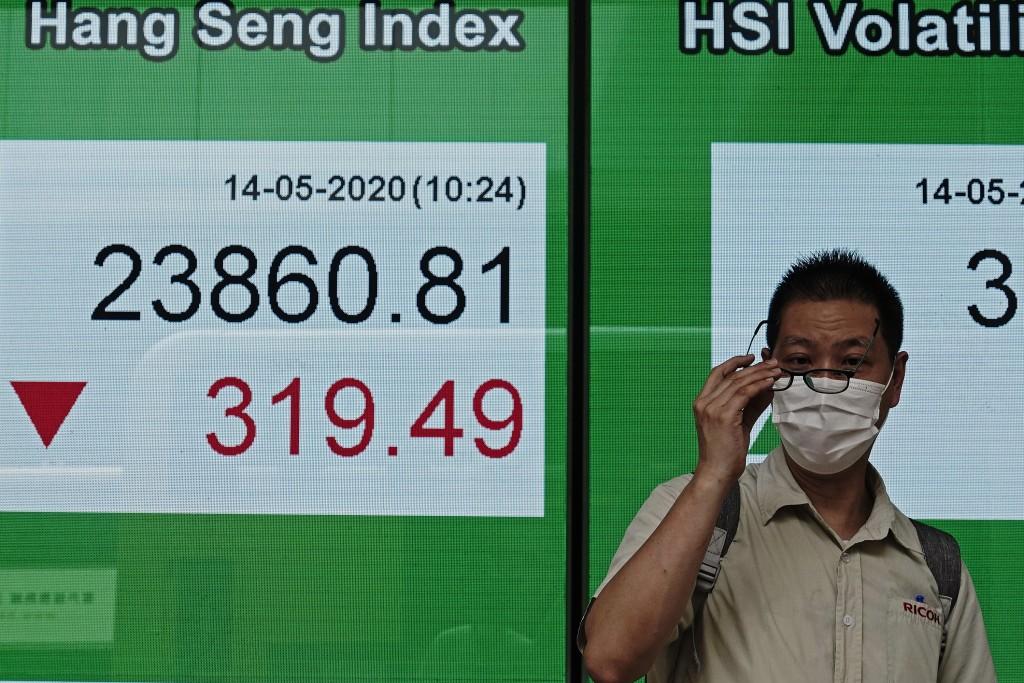 A man wearing face mask walks past a bank electronic board showing the Hong Kong share index at Hong Kong Stock Exchange Thursday, May 14, 2020. Asian...