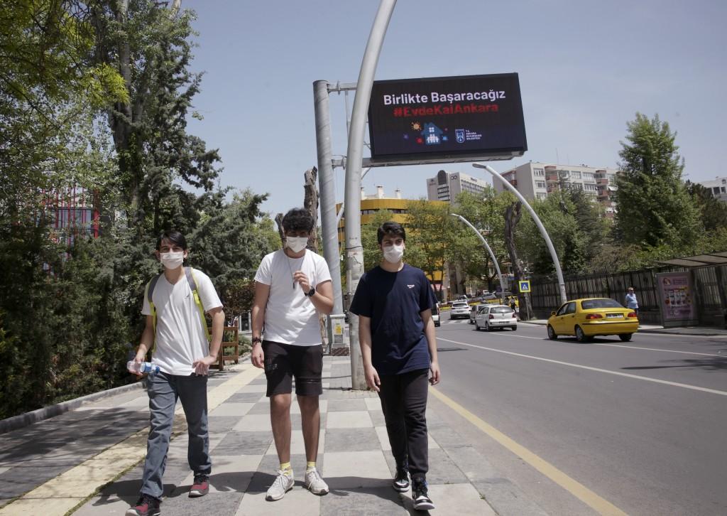 Turkish teenagers, from left, Berke Altuncu, 15, Ceyhun Gultekin,16, and Emirhan Ozdemir, 15, wearing face masks for protection against the coronaviru...
