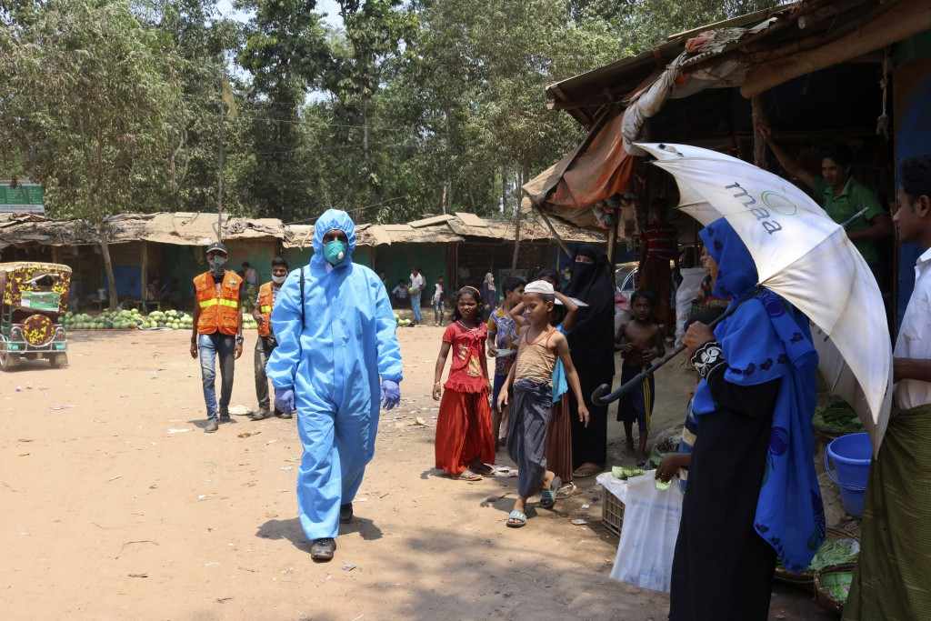 FILE - In this April 15, 2020, file photo, a health worker from an aid organization walks wearing a hazmat suit at the Kutupalong Rohingya refugee cam...
