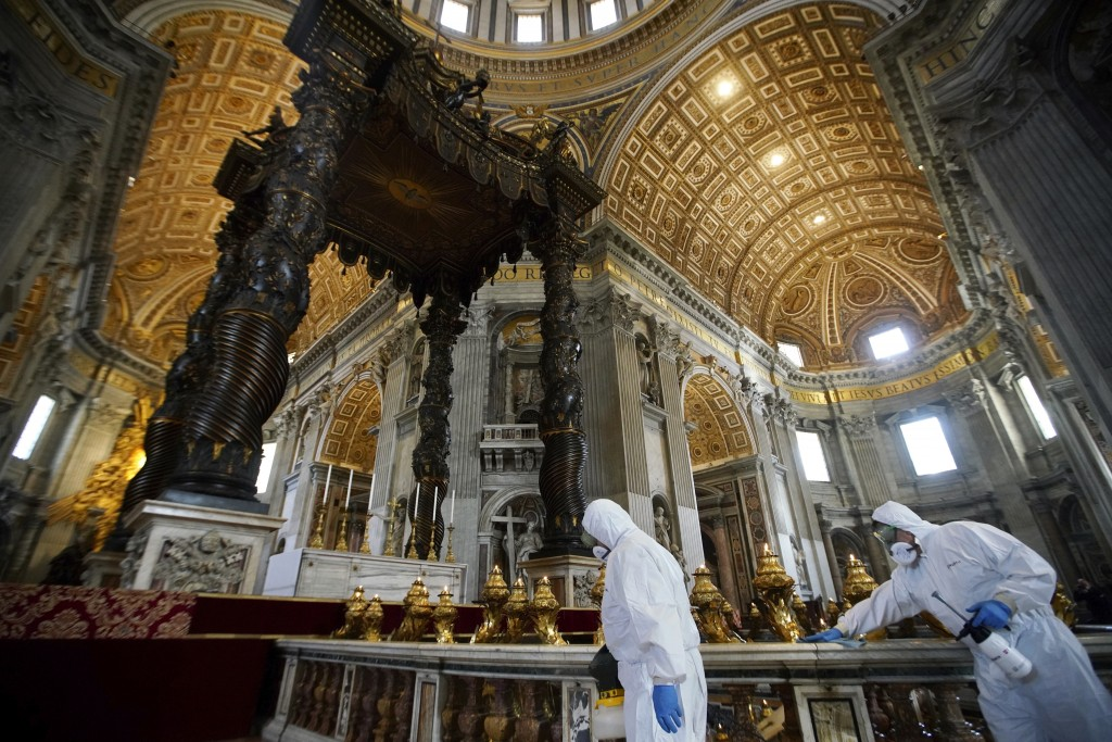 Workers in protective gear sanitize beneath the baroque sculpted bronze canopy of St. Peter's Baldachin inside St. Peter's Basilica, at the Vatican, F...