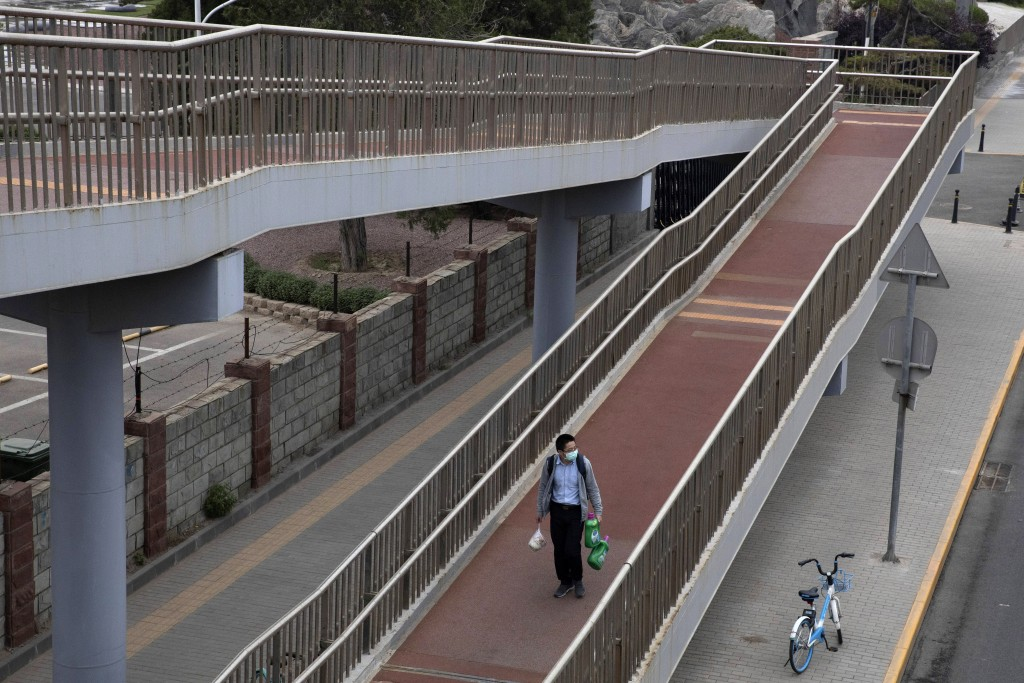 A man carrying his shopping walks down a pedestrian bridge in Beijing on Friday, May 15, 2020. Factory output rose in April as China's virus-battered ...