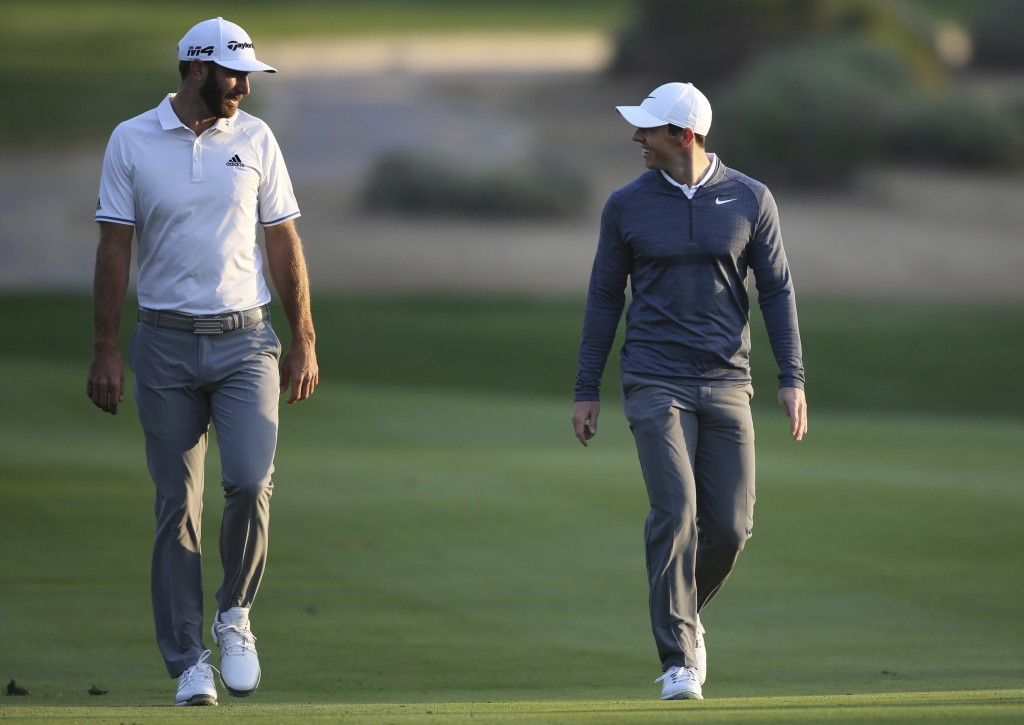 FILE - In this Jan. 18, 2018, file photo, Dustin Johnson of the United States, left, and Rory McIlroy of Northern Ireland talk on the 10th fairway dur...