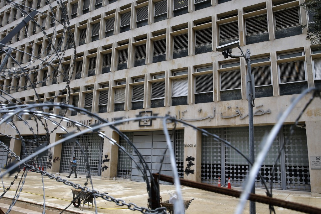 In this Wednesday, March 18, 2020 photo, a worker walks outside the Lebanese Central Bank that has been shut down as part of the preventive measures a...