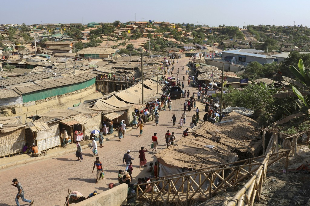 CORRECTS DATE - FILE - In this April 12, 2020, file photo, Rohingya refugees walk through one of the arterial roads at the Kutupalong refugee camp in ...