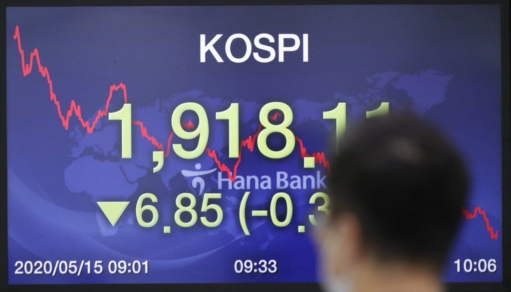 A currency trader walks near a screen showing the Korea Composite Stock Price Index (KOSPI) at the foreign exchange dealing room in Seoul, South Korea...