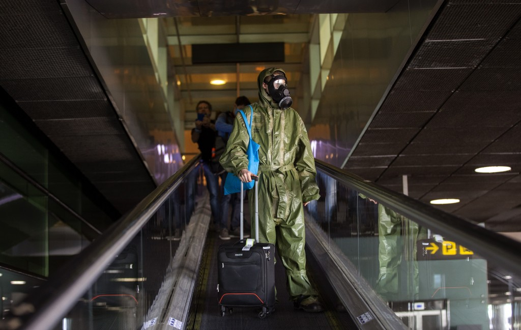 A passenger wearing a full protective suit arrives from London at the Barcelona airport, Spain, on Friday, May 15, 2020. Travellers arriving in Spain ...