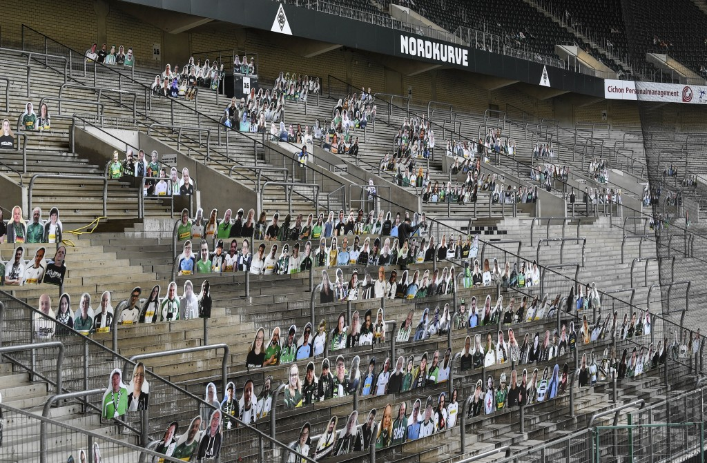 FILE - In this Thursday, April 16, 2020 file photo, portraits of fans of German Bundesliga soccer club Borussia Moenchengladbach are set on the suppor...
