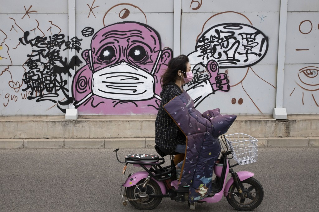 "A woman wearing a mask against the coronavirus rides past graffiti with the words ""Wear your mask properly"" in Beijing on Friday, May 15, 2020. Factor..."