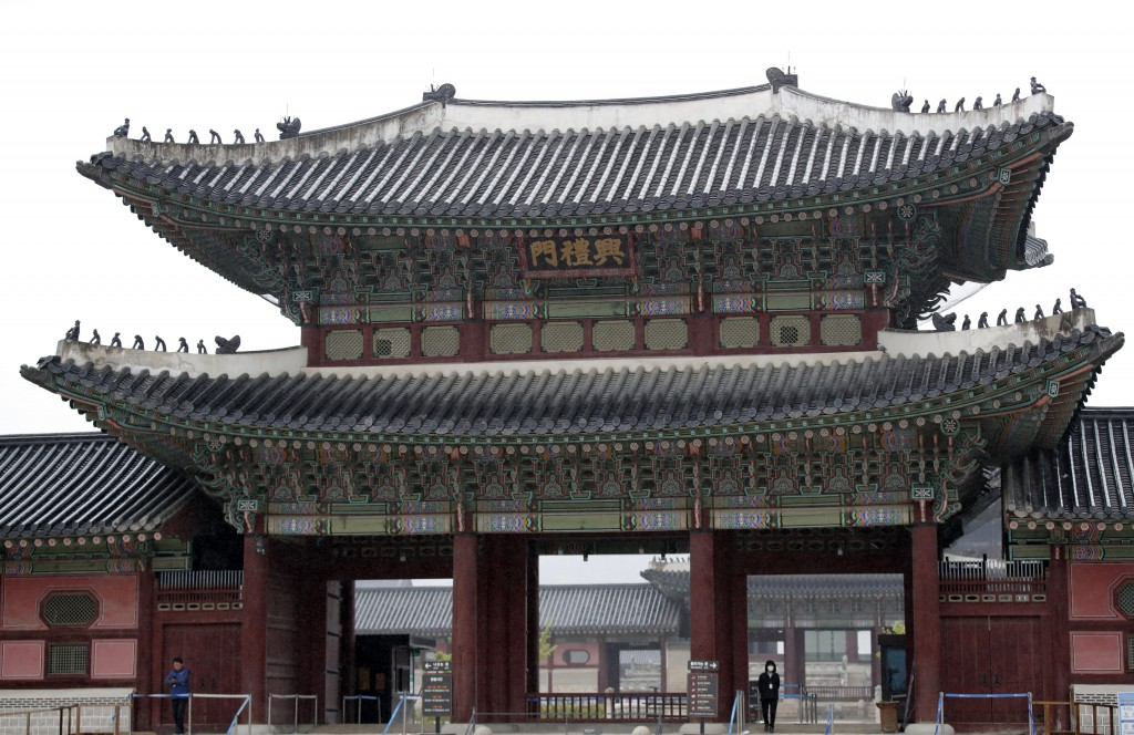 An employee, right bottom, wearing mask as a precaution against the new coronavirus, stands at the Gyeongbok Palace, the main royal palace during the ...