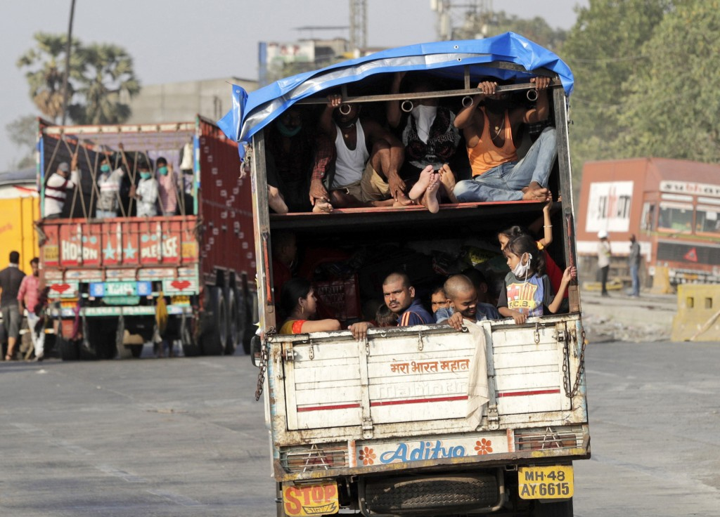 A truck carrying migrant workers leaves for Uttar Pradesh state, on the outskirts of Mumbai, India, Thursday, May 14, 2020. The pandemic has exposed I...