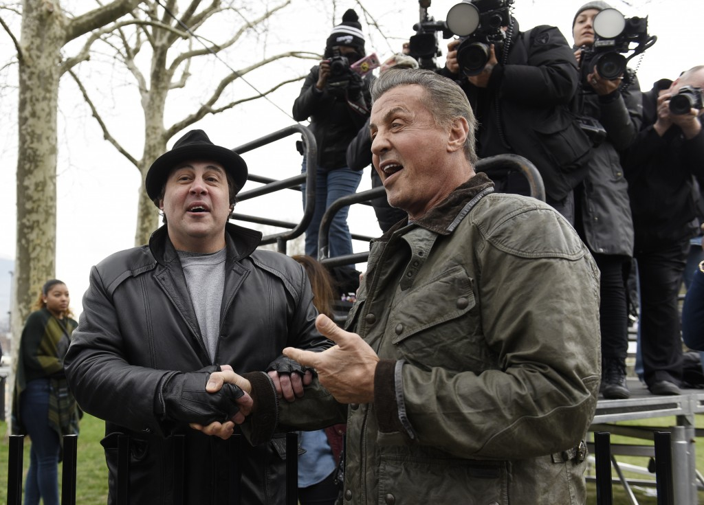 """FILE - In this April 6, 2018, file photo, Sylvester Stallone, right, greets Rocky impersonator Mike Kunda at a photo op for """"Creed II"""" in Philadelphia..."""