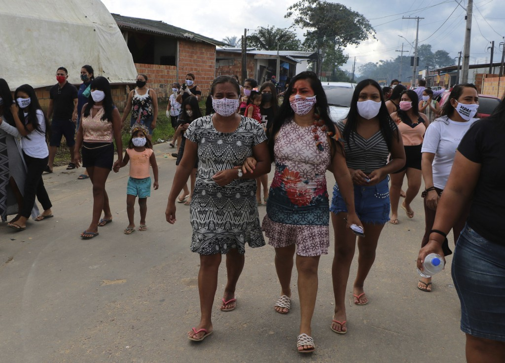 Locals walk after the funeral of Chief Messias Martins Moreira, 53, of the Kokama ethnic group, who died of Covid-19, at Parque das Tribos in Manaus, ...