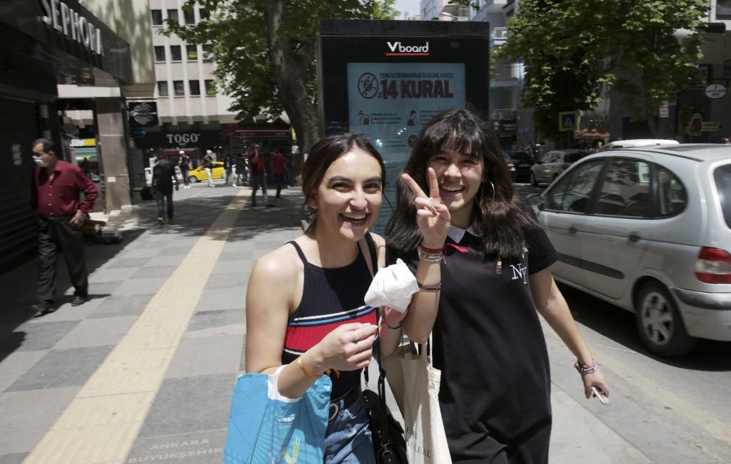 Two young girls pose for a photo as they walk in popular Tunali Hilmi Street amid the new coronavirus, in Ankara, Turkey, Friday, May 15, 2020. Teenag...