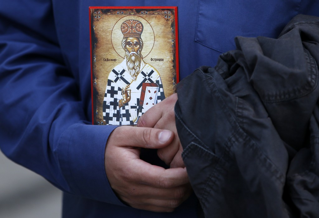 A man holds an icon during a protest after arrest of Serbian Orthodox Church priests in Montenegro, in Belgrade, Serbia, Thursday, May 14, 2020. Monte...