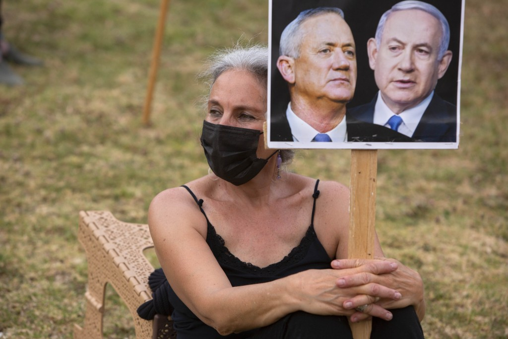 An Israeli woman holds a placard showing Israeli Prime Minister Benjamin Netanyahu and Blue and White party leader Benny Gantz, during a demonstration...