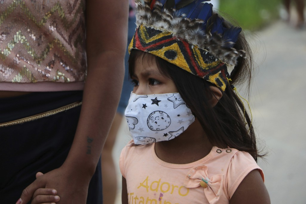 A girl wearing a mask walks holding hands with an adult after the funeral of Chief Messias Martins Moreira, 53, of the Kokama ethnic group, who died o...