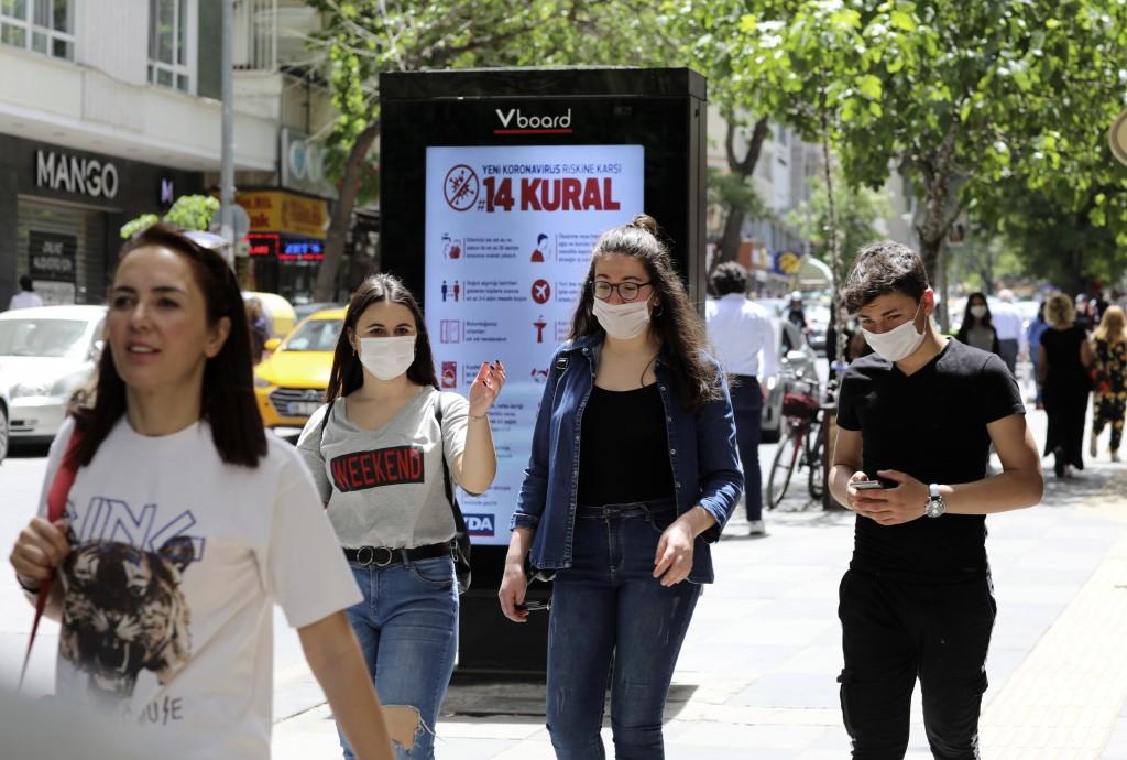 Turkish teenagers wearing face masks for protection against the coronavirus, walk in popular Tunali Hilmi, in Ankara, Turkey, Friday, May 15, 2020. Te...
