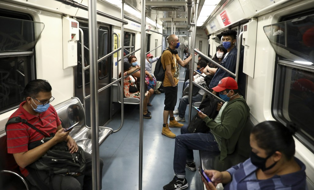 Commuters wearing masks against the spread of the new coronavirus ride the subway in Mexico City, Thursday, May 14, 2020. (AP Photo/Eduardo Verdugo)