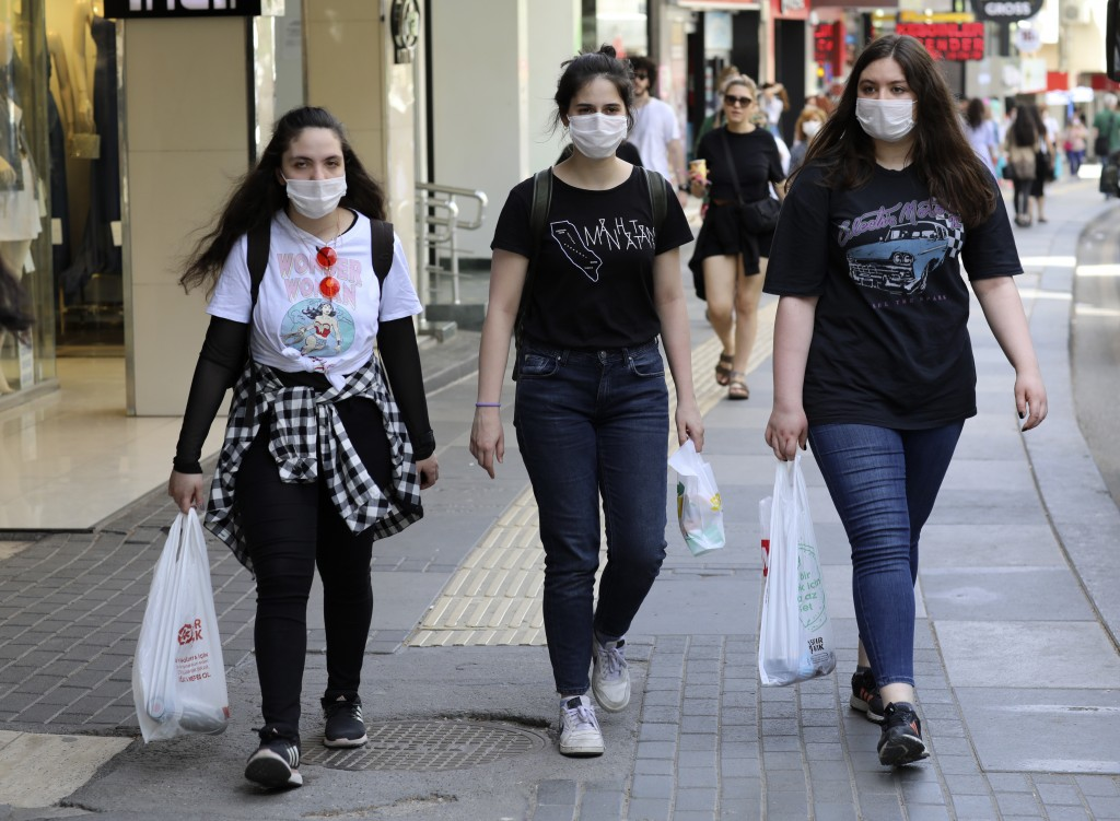 Young Turkish girls walk in popular Tunali Hilmi Street amid the new coronavirus, in Ankara, Turkey, Friday, May 15, 2020. Teenagers were able to leav...