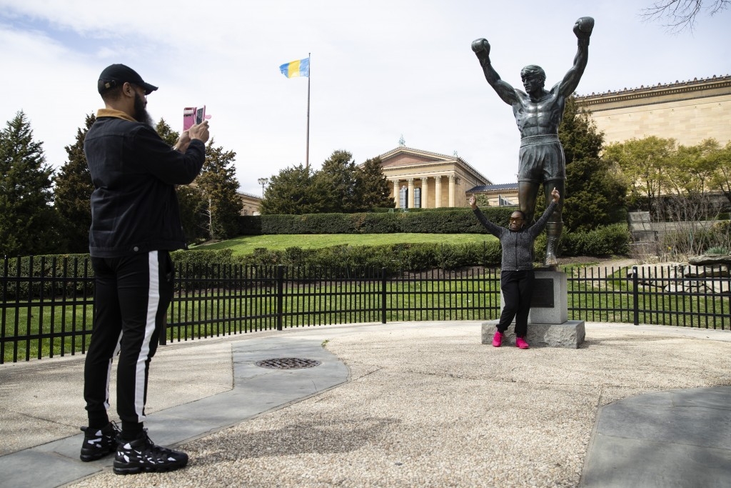 In this April 3, 2020 photo Lionel McGhee photographs his wife Tanyell Blake McGhee with the Rocky Statue at the Philadelphia Art Museum in Philadelph...