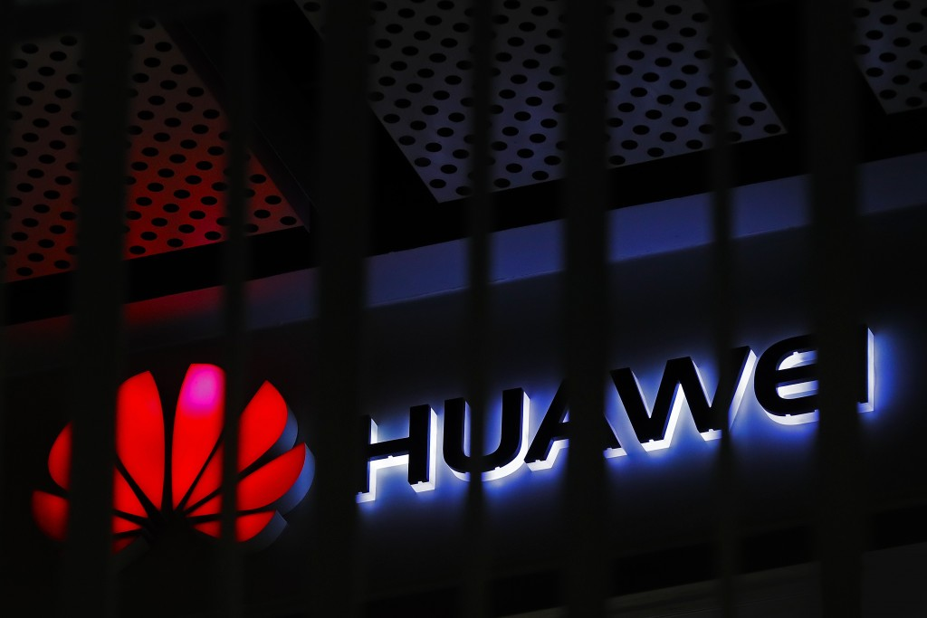 FILE - In this March 8, 2019, file photo, A logo of Huawei retail shop is seen through a handrail inside a commercial office building in Beijing.  The...