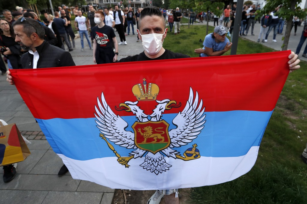 A man holds an old Montenegro flag during a protest after arrest of the Serbian Orthodox Church priests in Montenegro, in Belgrade, Serbia, Thursday, ...