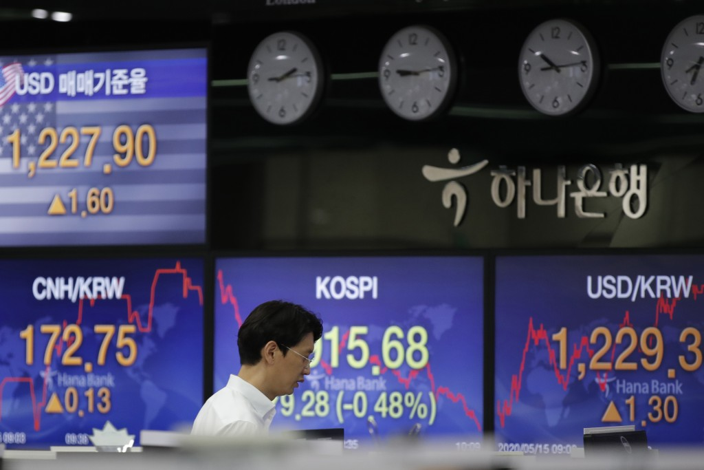 A currency trader walks near the screens showing the Korea Composite Stock Price Index (KOSPI), center, and the foreign exchange rates at the foreign ...