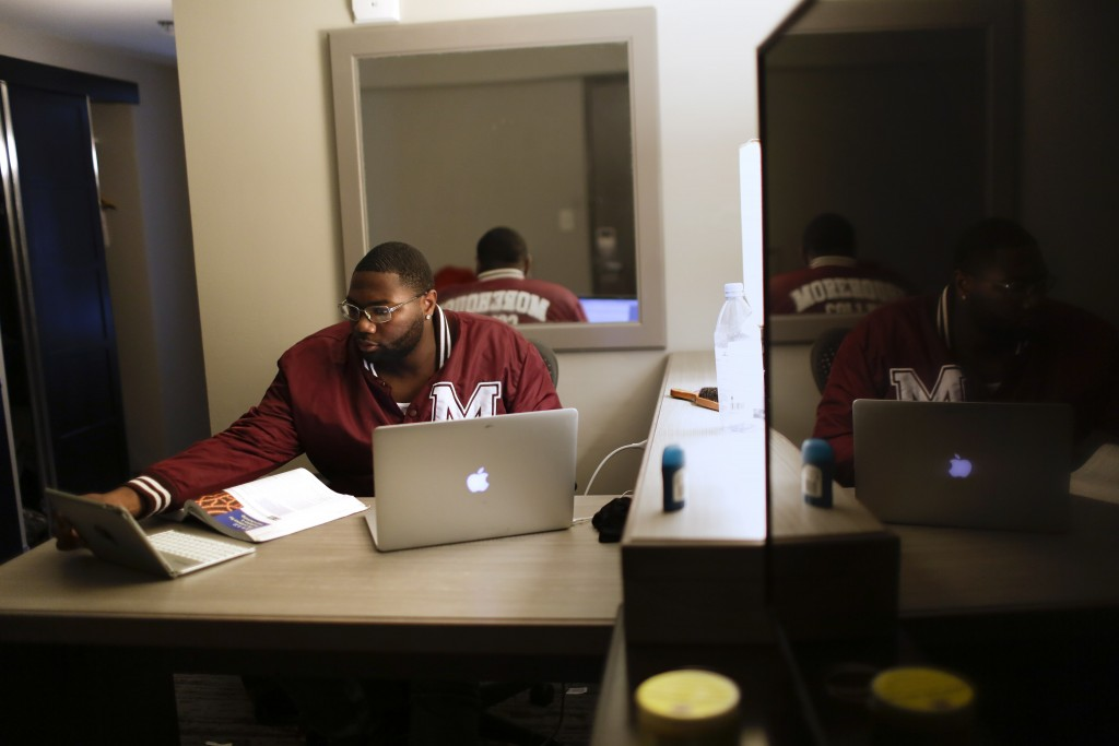 """In this Tuesday, May 5, 2020, photo, Morehouse College senior Lanarion """"LTL"""" Norwood Jr., of Atlanta, works on his computer in a hotel room in Atlanta..."""