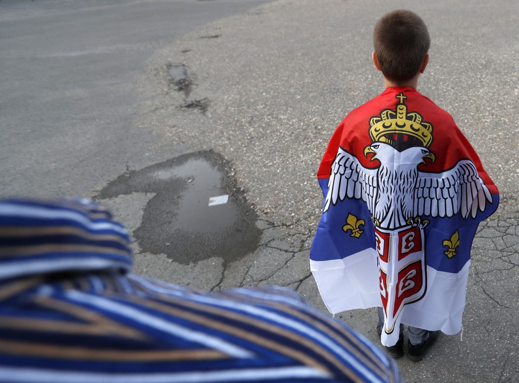 A boy with an old Montenegro flag attends during a protest after arrest of the Serbian Orthodox Church priests in Montenegro, in Belgrade, Serbia, Thu...