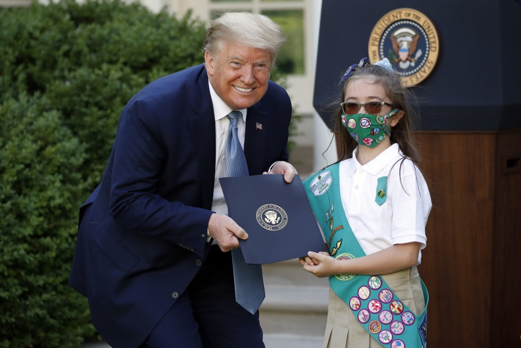 President Donald Trump poses for a photo with Girl Scout Troop 744 member Lauren Matney during a presidential recognition ceremony in the Rose Garden ...