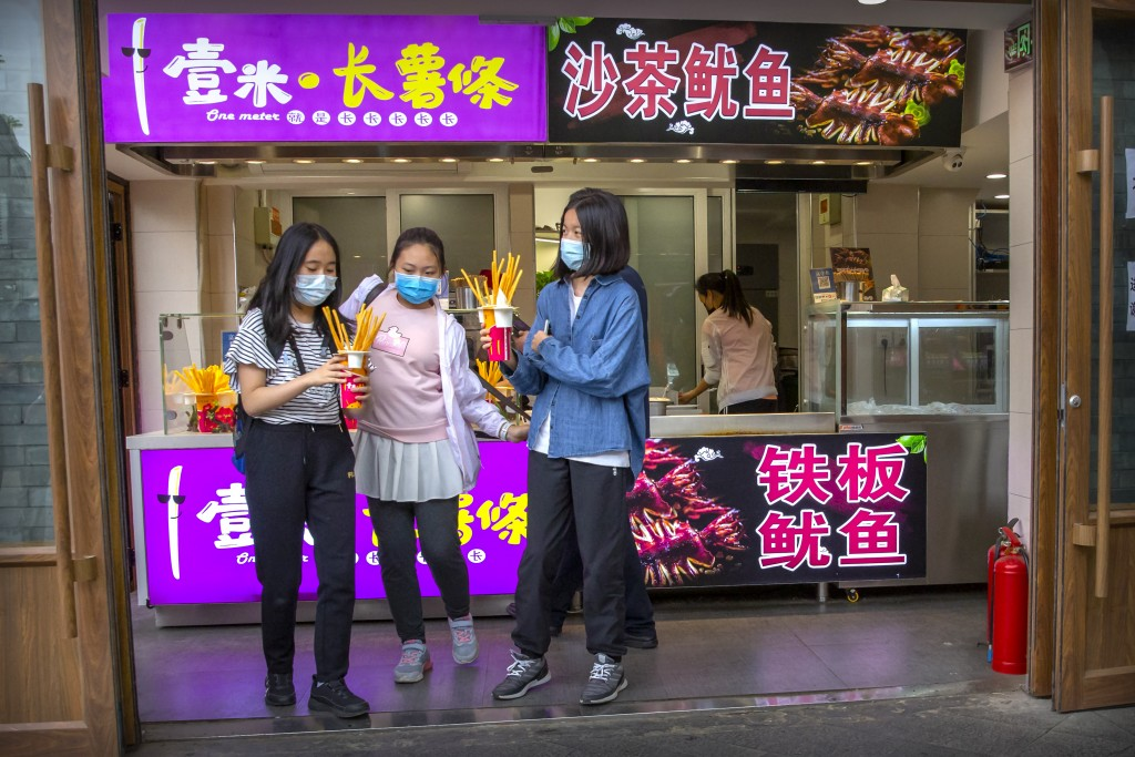 People wearing face masks to protect against the spread of the new coronavirus buy snacks at a shop on a pedestrian shopping street in Beijing, Saturd...