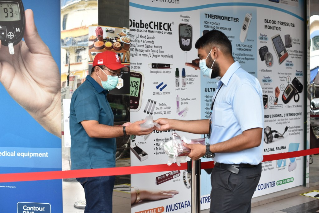 A security guard hands out disposable gloves to a man outside the supermarket section of the Mustafa Center on Saturday, May 16, 2020 in Singapore's L...