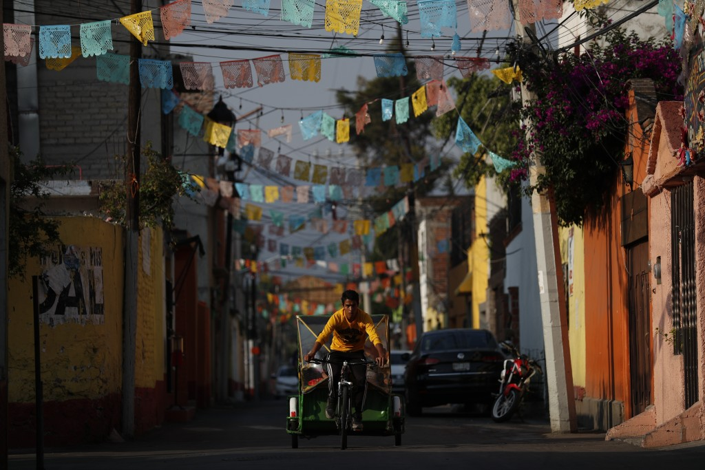 A bicycle taxi driver transports customers through the Xochimilco district of Mexico City, Friday, May 15, 2020. As Mexico moves toward a gradual reac...
