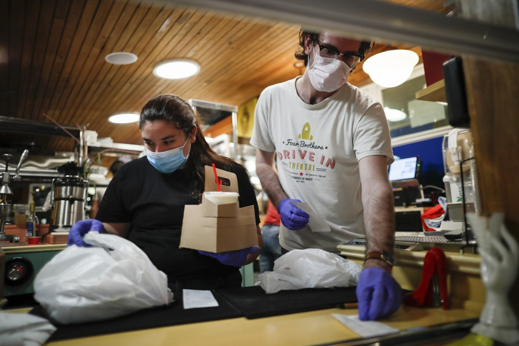 Workers man the take-out food station while wearing protective equipment at the Four Brothers Drive In Theatre, Friday, May 15, 2020, in Amenia, N.Y.,...